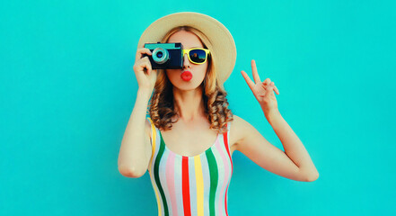 Portrait of young woman photographer with vintage film camera blowing red lips sending sweet air kiss wearing a summer straw hat over blue background
