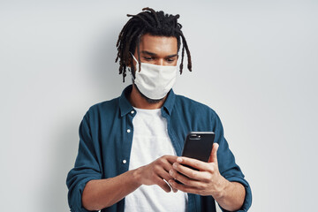 Careful young African man wearing medical face mask and using smart phone while standing against...