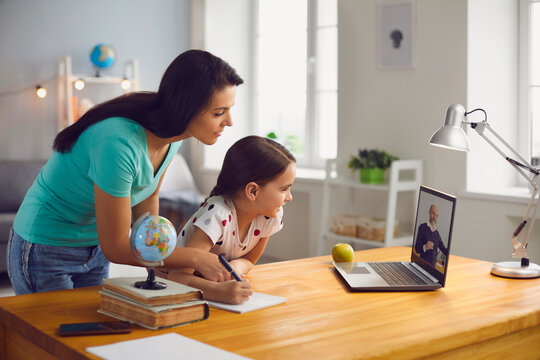 Distance education. Mother and daughter watching online video conference with mature teacher on laptop at home