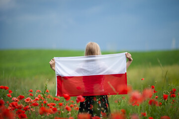 Blond girl holding flag of Poland in the poppy field. Back  view. Polish Flag Day. Independence...
