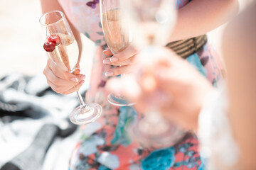 Close up clinking, cheers. Seasonal feast at beach resort. Group of friends celebrating, resting, having fun in sunny summer day. Look happy and cheerful. Festive time, wellness, holiday, party.