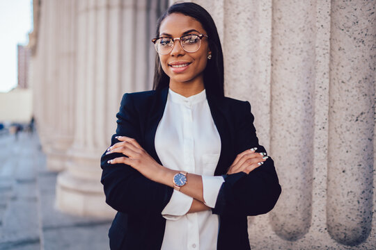 Half length portrait on successful businesswoman dressed in formal wear folding hands and looking at camera.Prosperous professional financial manager in eyewear smiling at camera standing outdoors