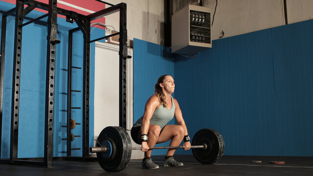 Young strong woman lifting heavy weights in grungy gym.