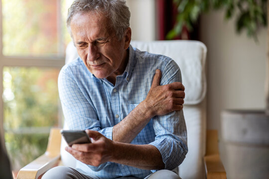 Senior man experiencing pain while using a smartphone at home