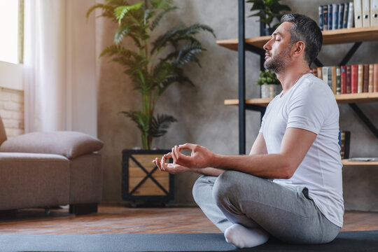 Meditation concept. Calm man meditating while sitting in lotus position relaxing doing yoga at home