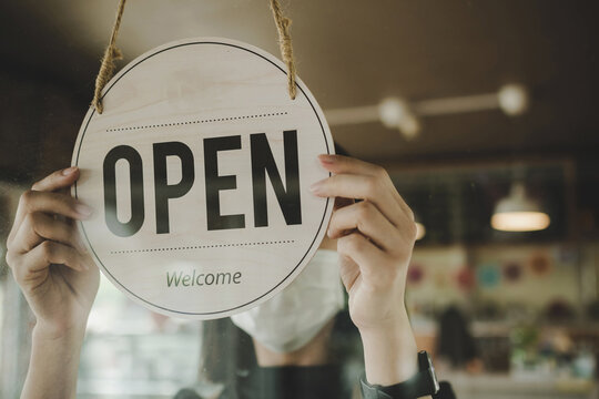Open. barista, waitress woman wearing protection face mask turning open sign board on glass door in modern cafe coffee shop, cafe restaurant, retail store, small business owner, food and drink concept