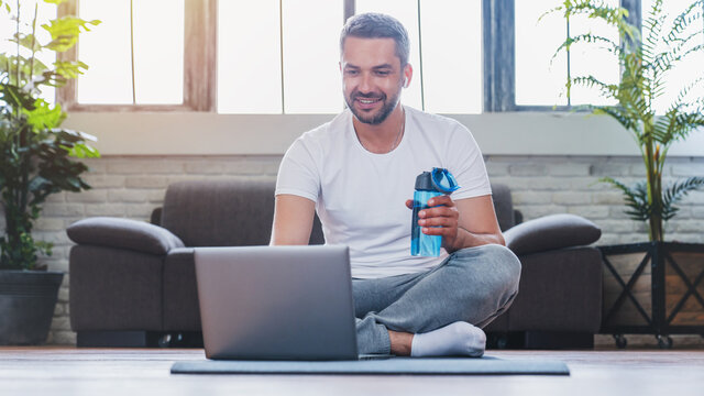 Handsome adult man using laptop and drinking water while having break during workout at home