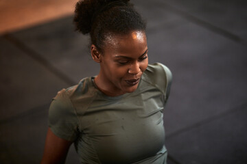 Fit young woman sweating while sitting in a gym