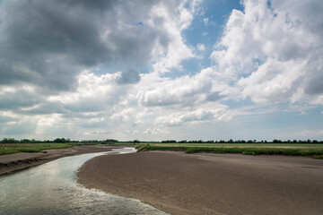 A cloudy, summer, three image HDR of the River Wampool in north west Cumbria, England, at low tide.