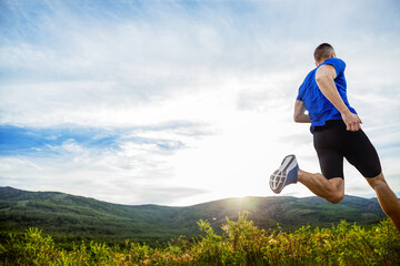 Foto op Canvas Jogging back athlete runner run mountain meadow in rays of sunset