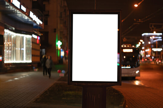 Advertising vertical billboard in the city glows at night. MOCKUP for design
