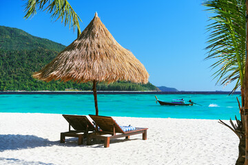 Beautiful tropical beach with two sun loungers and straw umbrella