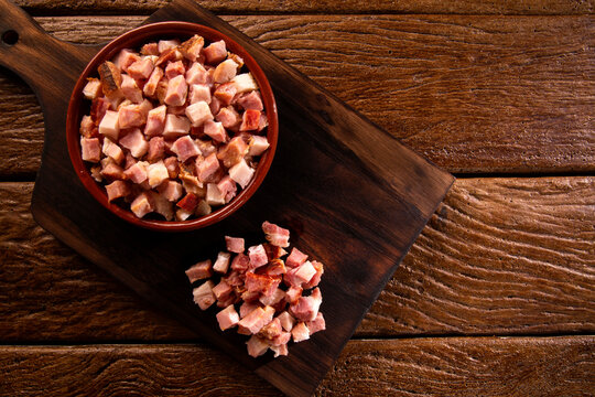 closeup of cubes of bacon on a rustic wooden board. Raw