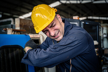 Factory worker got his arm stuck in the machine. Workplace accident. occupational hazard.