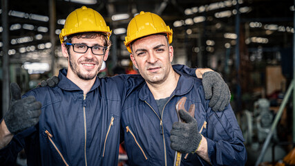 Two workers in blue jumpsuits with yellow hard hats smiling. Confident mechanics ready for work.