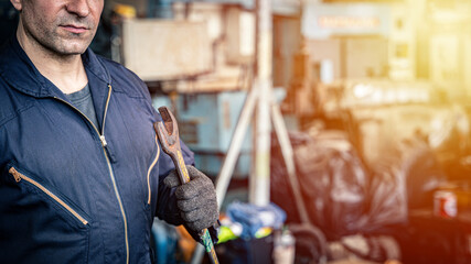 Man in blue jumpsuit holding metal wrench in the in the factory. Confident mechanic ready for work.
