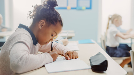 In Elementary School Classroom Brilliant Black Girl Writes in Exercise Notebook, Taking Test. Junior Classroom with Diverse Group of Bright Children Working Diligently and Learning. Side View Portrait