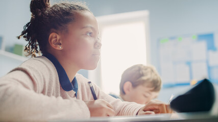 In Elementary School Classroom Black Girl Writes in Exercise Notebook, Taking Test. Junior Classroom with Diverse Group of Bright Children Working Diligently, Learning. Low Angle Side View Portrait