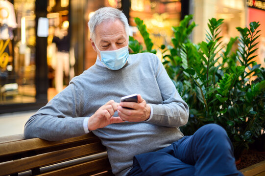 Senior man sitting on a bench and using a smartphone in a mall wearing mask, coronavirus concept