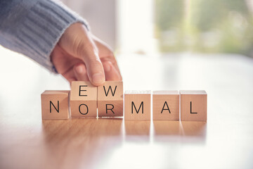 Woman hand arranging wooden cubes with NEW NORMAL word. Adapting to new life or business...