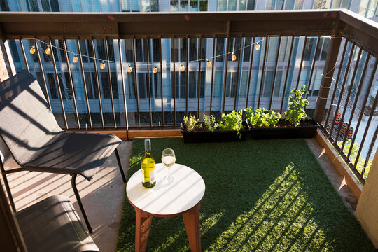 Apartment balcony in city with grass turf and potted plants. Evening light.