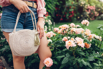 Stylish female handbag. Young woman holding beautiful summer accessories in garden outdoors. City fashion