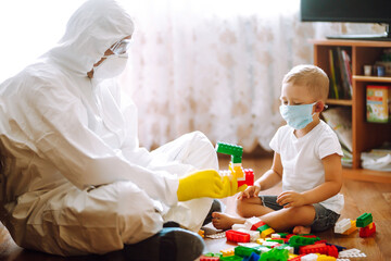 Man in protective hazmat suit plays constructor with little child in medical mask. The concept of...