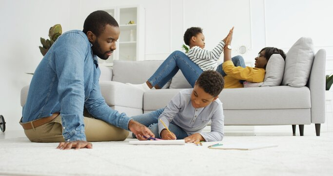 Happy african american family spending time together at home.