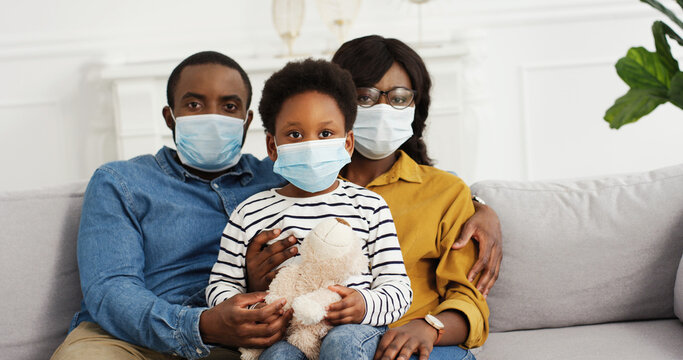 African american parents with cute small daughter wearing protective masks at home. Stop the virus and epidemic diseases.
