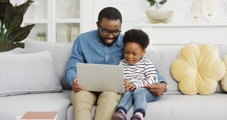 Portrait of african american father sitting with daughter on sofa using laptop watching video.