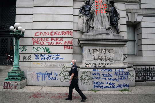 """A court officer walks past a wall of graffiti across from a protest to defund the police in a place they are calling the """"City Hall Autonomous Zone"""" in support of """"Black Lives Matter"""" in the Manhattan borough of New York City"""
