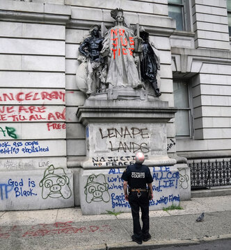 """A court officer looks at a wall of graffiti across from a protest to defund the police in a place they are calling the """"City Hall Autonomous Zone"""" in support of """"Black Lives Matter"""" in the Manhattan borough of New York City"""