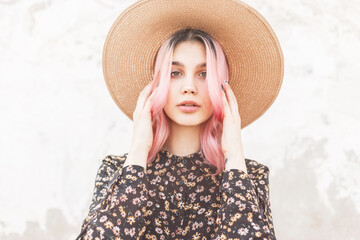 Portrait tender young pretty woman with beautiful pink hair in fashionable straw hat in stylish...