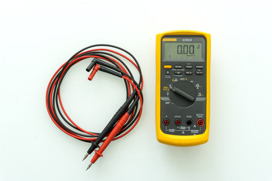 Yellow Digital multimeter with probes for measuring voltage, current, resistance on white background , A multimeter is an electronic measuring instrument.