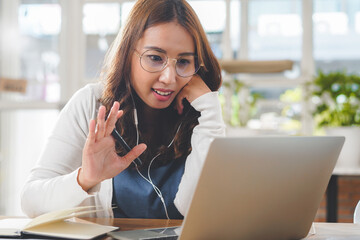 Woman waving hands greeting colleagues in video conference meeting during work from home.