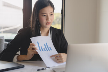Asian young business woman holding paperwork and video calling via laptop talk to client