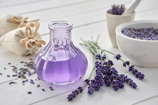 Dry lavender flowers, bottle of essential oil or flavored water, sachet and mortar on white wooden table.