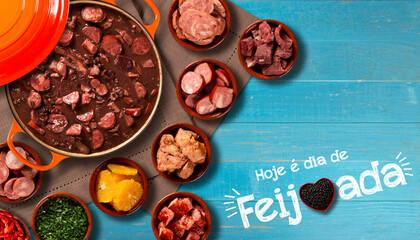 Brazilian Feijoada Food in red heart bowl. Written Today is feijoada day in Portuguese. Top view.