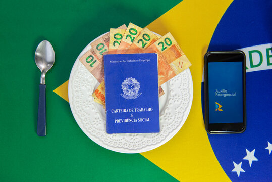 Money in Work Card and Cell Phone with the image of the Emergency Aid (Auxilio Emergencial) plan Brazilian dish of food. Concept of social aid to the neediest.