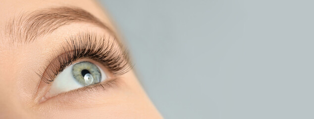 Closeup view of young woman with beautiful long eyelashes on grey background, space for text....
