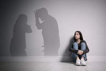 Upset teenage girl sitting on floor near wall and silhouettes of arguing parents