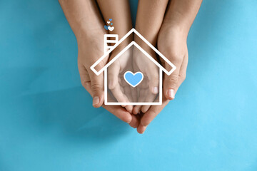 Illustration of house and happy family holding hands on blue background, top view