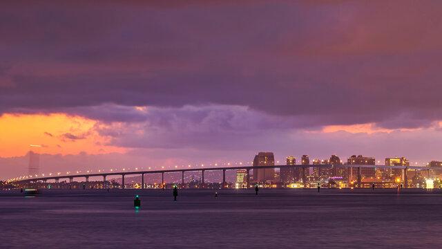 Urban city skyline under a cloudy twilight sky. View of the Coronado Bay Bridge and Downtown San Diego skyline from across a bay of water.