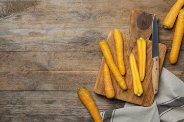 Fototapete - Raw yellow carrots, cutting board and knife on wooden table, flat lay. Space for text