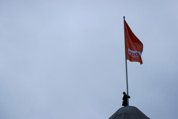 A Greenpeace activist holds onto a flag pole on the roof of the headquarters of the party Christian Democratic Union (CDU) in Berlin
