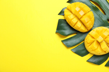 Fototapete - Cut fresh ripe mango and leaf on yellow background, flat lay. Space for text