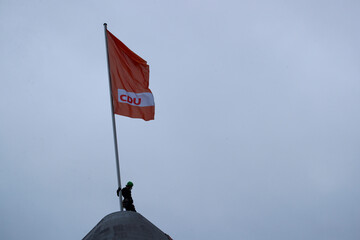 A Greenpeace activist stands next to a flag pole on the roof of the headquarters of the party Christian Democratic Union (CDU) in Berlin