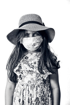 5 year old girl wearing a sun hat and a flower dress and mask, black and white on a white background.