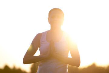 silhouette of a woman doing yoga in the fresh air. The concept of a healthy lifestyle. Outdoor recreation. Meditation and yoga classes
