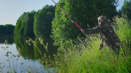 Wall Mural - Woman fishing. Elderly angler woman fishing on the calm summer pond during sunset